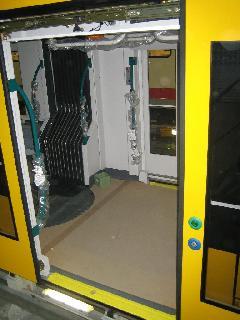 Az 1300 mm széles, kifelé nyíló lengőajtón belépve fűtött padlójú térrészbe érkezik az utas. Jól látható a normál (zöld) és a kerekesszékes (kék) ajtónyitó., Siemens-SGP gyár, Bécs (forrás: Siemens)