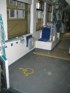 Az egyik kerekesszékes hely a kettőből. A kísérő számára lehajtható ülés, a falon külön leszállásjelző. A kerekek fölötti középső ülések esetén kicsi a lábtér. Látható a kicsi ablaknyílás is., Siemens-SGP gyár, Bécs (forrás: Siemens)