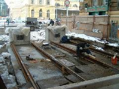 Ehelyett: Betonbakokkal zárják le a Festetics utca kijáratát, szimbolikusan jelezve, hogy a villamos innen nem megy tovább soha többet. Betont a sínek közé, ehhez ért, ennyit tud a magát szakmának nevező metrós és autóslobbi, melyek fő gyűjtőhelye a kiskirályságként viselkedő DBR Metró Igazgatóság és baráti köre, a velük szimbiózisban élő néhány közlekedéstervező cég., Festetics utca, Budapest (forrás: Nagy Dániel)