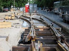 A Móricz Zsigmond körtéri új végállomás kitérőcsoportjának építése. Való igaz, ez a megoldás egy keresztezéssel kevesebb, mint az ilyen helyen szokásos vágánykapcsolat (négy váltó, középütt kereszt), ám több helyet foglal, így a villamosok ha feltorlódnak, belóghatnak a Bercsényi utcai kereszteződésbe. A hurok mind forgalmilag, mind az átszállások közelsége szempontjából jobb volt. A síneket ráadásul annyira nem süllyesztik be (itt lejtős a terep), hogy vízszintes legyen a végállomás, ám arra figyeltek, hogy a továbbvezetésük lehetetlenné váljon., Karinthy Frigyes út, Budapest (forrás: Hajnal Gergely)
