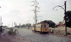A 65-66-os szerelvény a Vágóhíd utcáról éppen lehalad a MÁV felüljárójáról. A háttérben az Attila téri templom látszik. Ezek a kocsik eredeti, Debrecen számára gyártott győri motorkocsik voltak, 1958-ban ikresítették őket a 13-as és 23-as motorkocsik felhasználásával. 1973-ban a szerelvényt szétszedték, a járművekből kiszerelték motorjaikat, és pótkocsiként ikerkocsik közé kapcsolták őket. 1975-ig közlekedtek, majd selejtezték őket. Sajnos egyetlen eredeti debreceni motorkocsi sem maradt fenn az utókor számára. , Vágóhíd utca, Debrecen (forrás: Michael Taplin)
