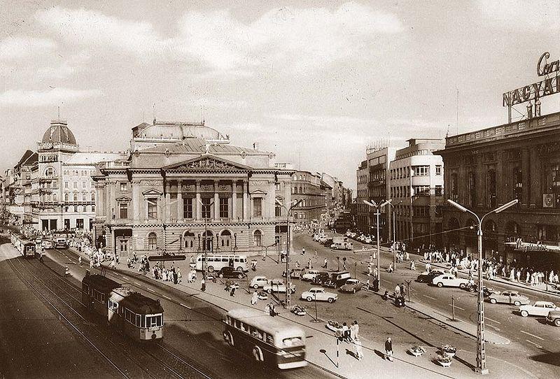 A Blaha Lujza tér. A kép készültekor még állt a Nemzeti Színház, és a Corvin áruház is eredeti pompájában tündökölt. A kép alján egy középbejáratú szerelvény látható, mely valószínűleg a 67-es viszonylatra volt beosztva